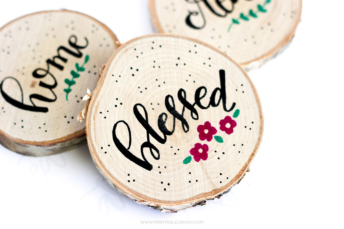 Hand Lettered Wood Coasters with the words love, blessed and flowers on them