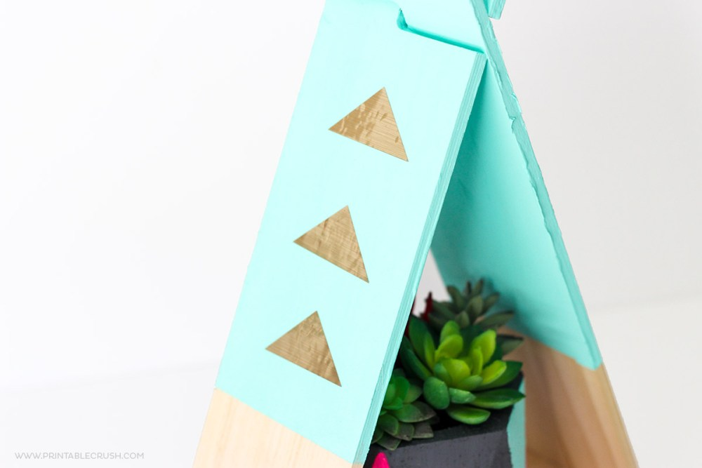 Wood slices shaped like a teepee painted teal with gold foil added.