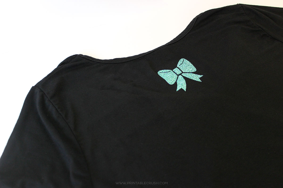 Close up of black shirt with teal iron-on vinyl bow