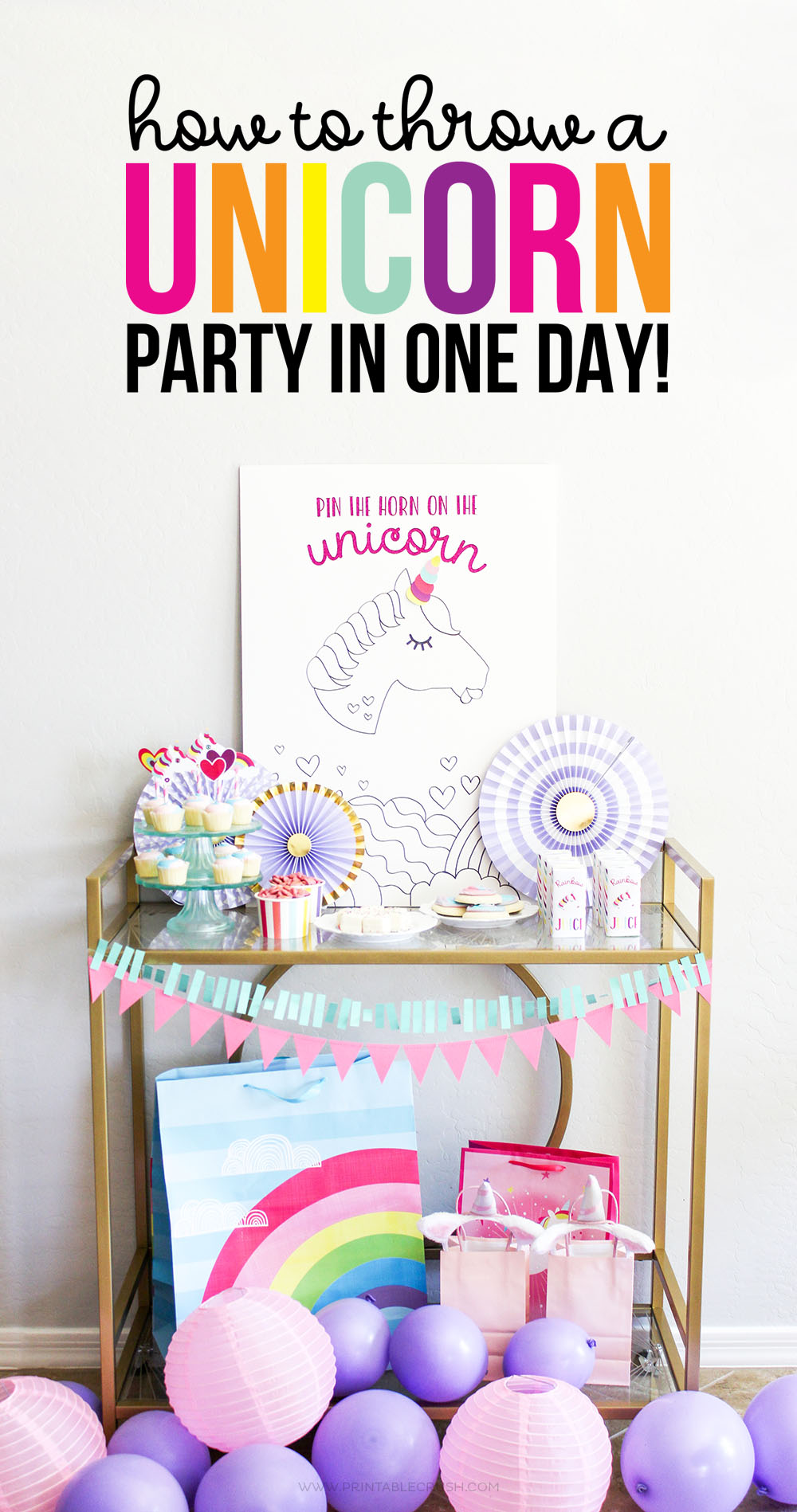 Party set up with multi-colored unicorn party supplies and purple balloons