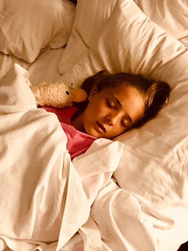 child-sleeping-white-sheets-with-doll