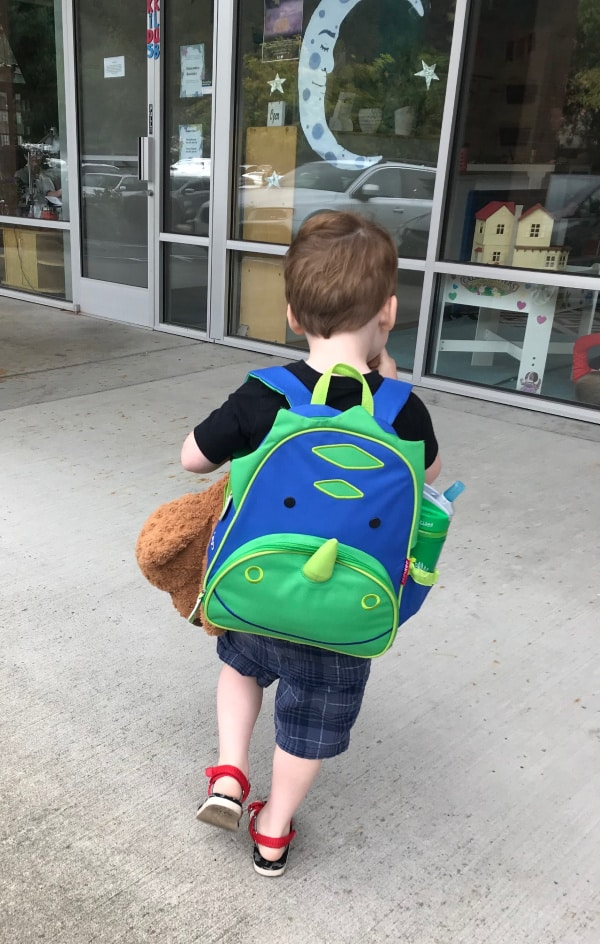 preschool-age-child-walking-into-school-with-toddler-dinosaur-backpack