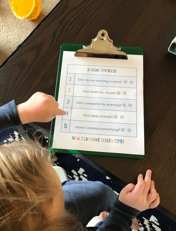 editable summer screen time checklist printable on green clipboard with a toddler pointing to it