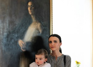 Greed 193x89 - the model and her baby standing in front of the painting