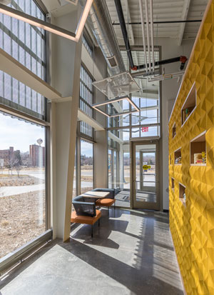 Perforated metal panels in front of the glass in the research lab's lobby provide sunshade, but also allow light to penetrate while simultaneously managing heat gain and glare from direct sunlight. Photo credit: David J. Turner Photography