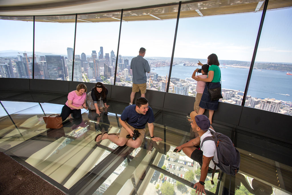 Guests sit on The Loupe - the Space Needle's newly-installed glass floor. Courtesy of John Lok and Space Needle LLC.