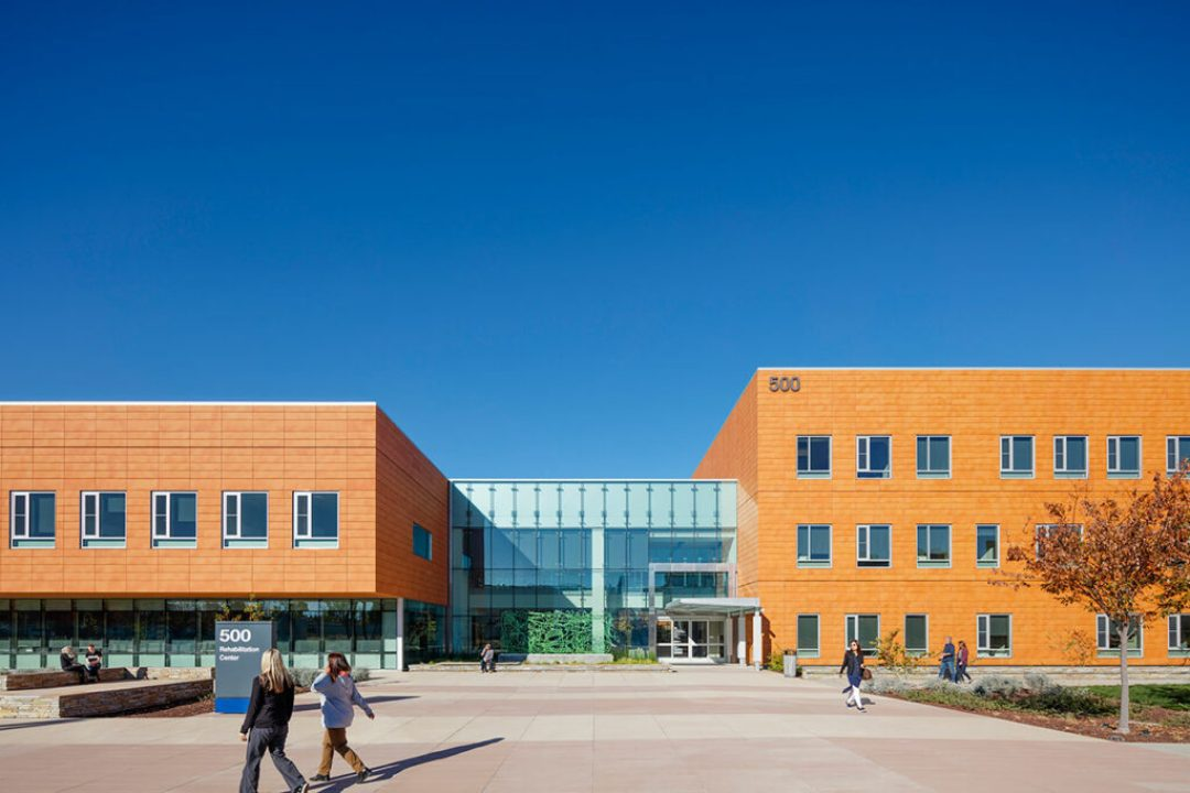 Main entrance: the simple terracotta façade echoes the campus' material pallet; the main entry quietly welcomes visitors, patients, and medical personnel. Photo: © Tim Griffith and Kyle Jeffers