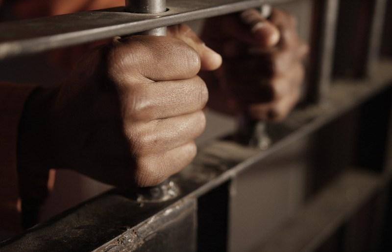 prisoner-holding-the-bars-of-his-cell-racial-profiling-of-young-black-men-in-america_t20_b8LekV.jpg