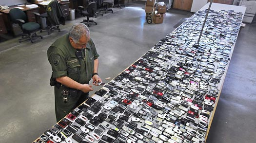 Correctional Officer Jose Sandoval inspects one of the more than 2,000 cell phones confiscated from inmates at Calfornia State Prison in Vacaville, California. Rich Pedroncelli / AP