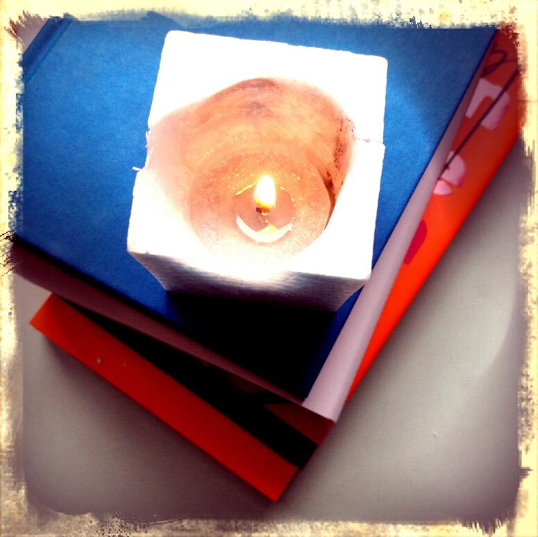 Kerze auf einem Bücherstapel