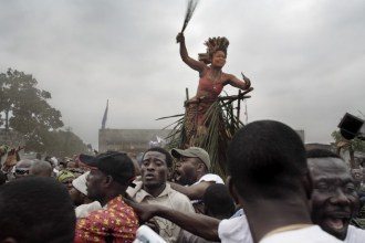 A traditional dancer and crowd salute Jean-Pierre Bemba as he walks to a rally from the airport, Kinshasa, July 2006.