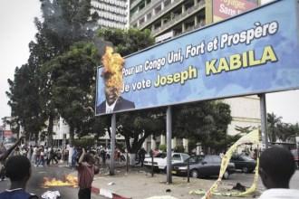 Followers of Etienne Tshisikedi, calling for a boycott of the elections, burn a Kabila election billboard, central Kinshasa.