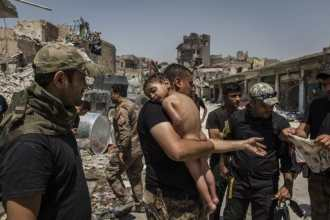 An unidentified young boy, who was carried out of the last ISIS controlled area in the Old City of Mosul by a man suspected of being a militant, is...