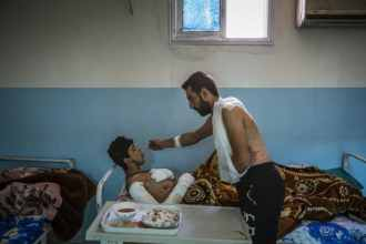 25-year-old Mohammed Sheko feeds his SDF comrade, 18-year-old Salah Al Raqawi, at a hospital for injured fighters in Kurdish controlled Syria. The...