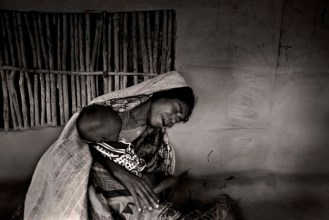 A mother grieves as her child lapses into unconsciousness. The tumour on her child's back has worsened. Her husband is fishing and will not return...
