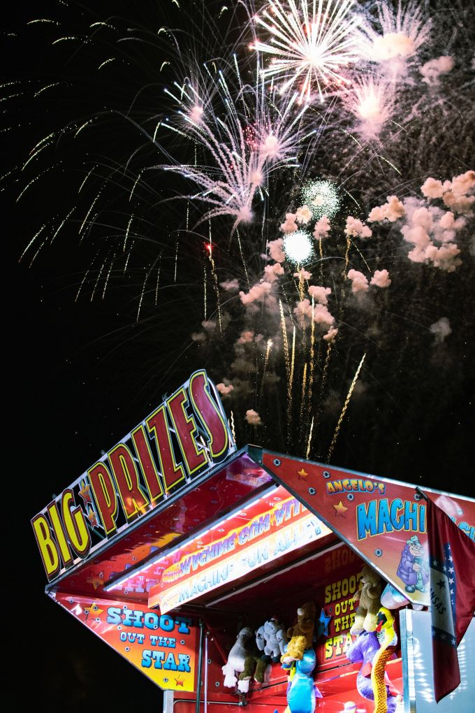 "Fairground attractions with ""Big Prizes"" sign and fireworks overhead"