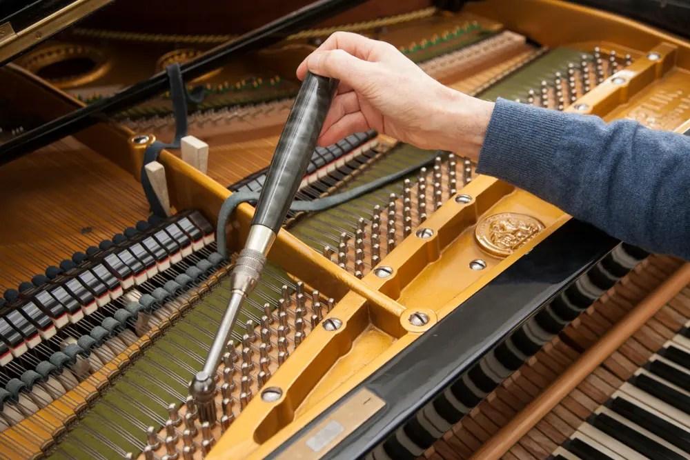 グランドピアノをチューニングするベテランの調律師