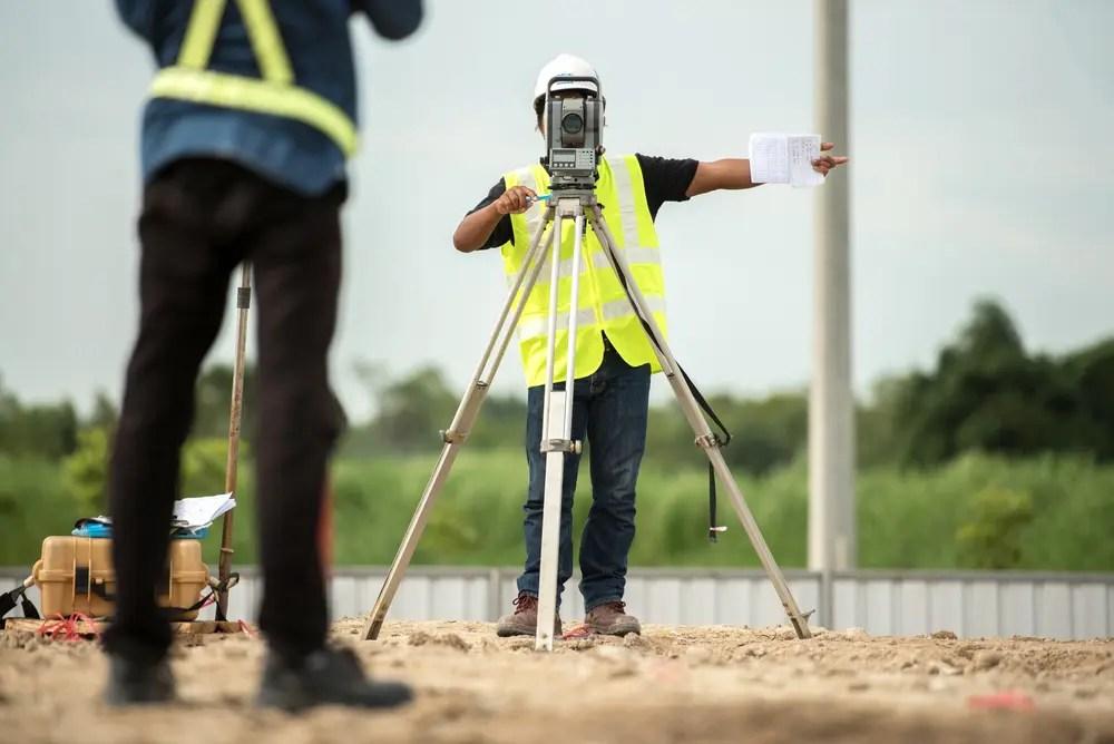 測量士の指示に従い測量する測量士補の男性