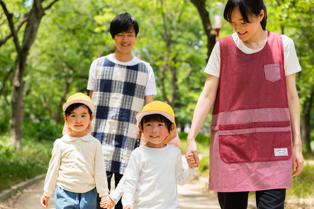 子どもを連れて公園を散歩する保育士の男女