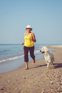 Elderly woman running with her golder retriever