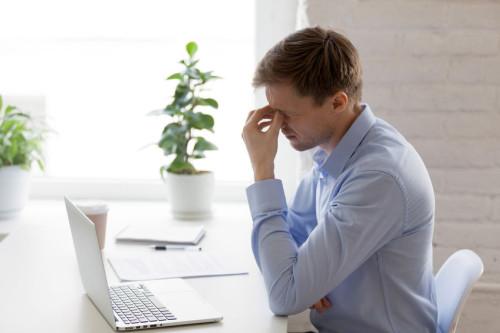 Tired businessman massaging nose bridge, feeling eyes strain