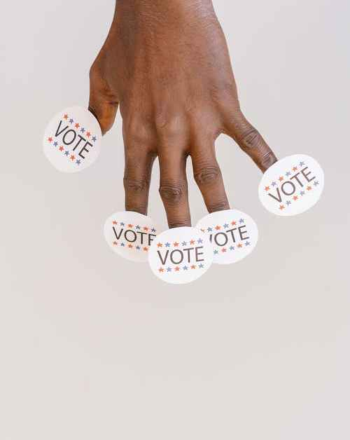 image showing hand with 5 voting stickers representing ranked choice voting