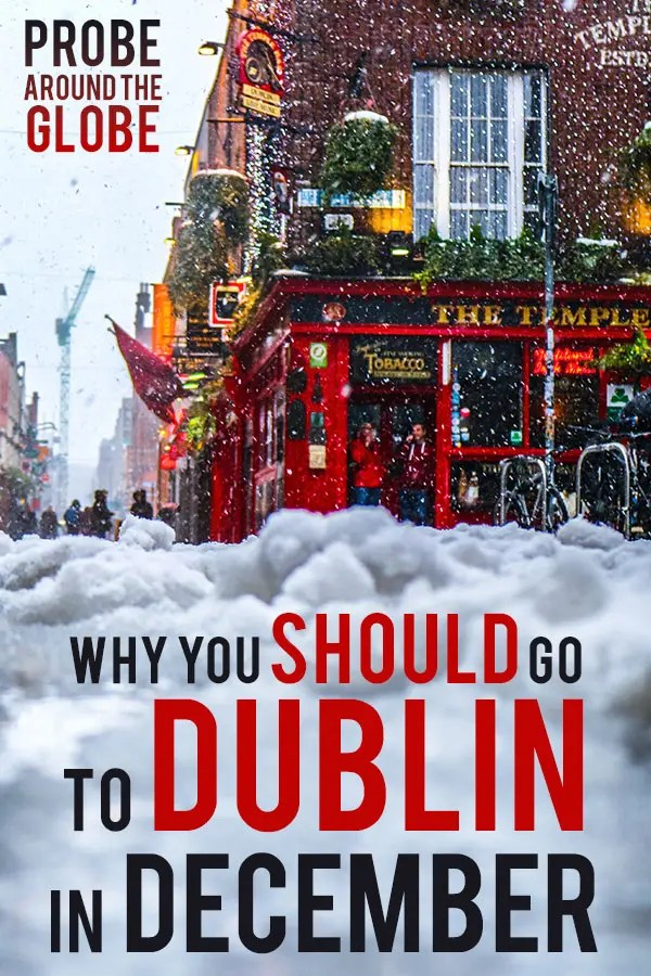 Moody image with snow falling down in front of the famous red pub in Dublin Ireland, the Temple Bar, which is decorated with Christmas lights and holly. Text overlay saying: Why you should go to Dublin in December. Probe around the Globe.