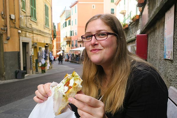 Eating foccaccia for breakfast in Riomaggiore. Do you plan to visit the popular 5 villages that make up the Cinque Terre in Italy? But how can you travel on the Cinque Terre train and what is the Cinque Terre Pass? I explain how to use the Cinque Terre Card to travel by train to the Cinque Terre train station in this ultimate guide for Cinque Terre Train Travel