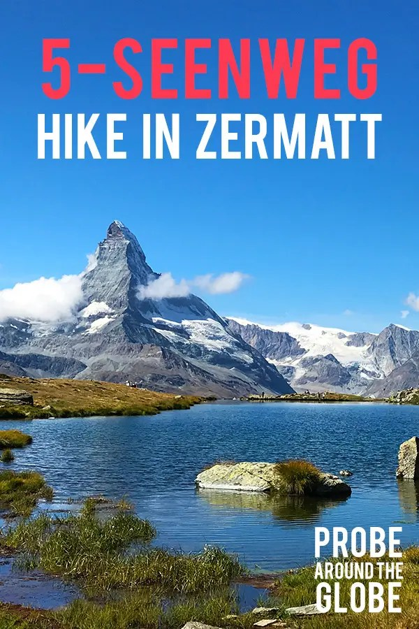 Scenic image of the Matterhorn mountain reflected in the water of Stellisee Switzerland under a clear blue sky with some small clouds. Text overlay saying: 5-Seenweg Hike in Zermatt. Probe around the Globe