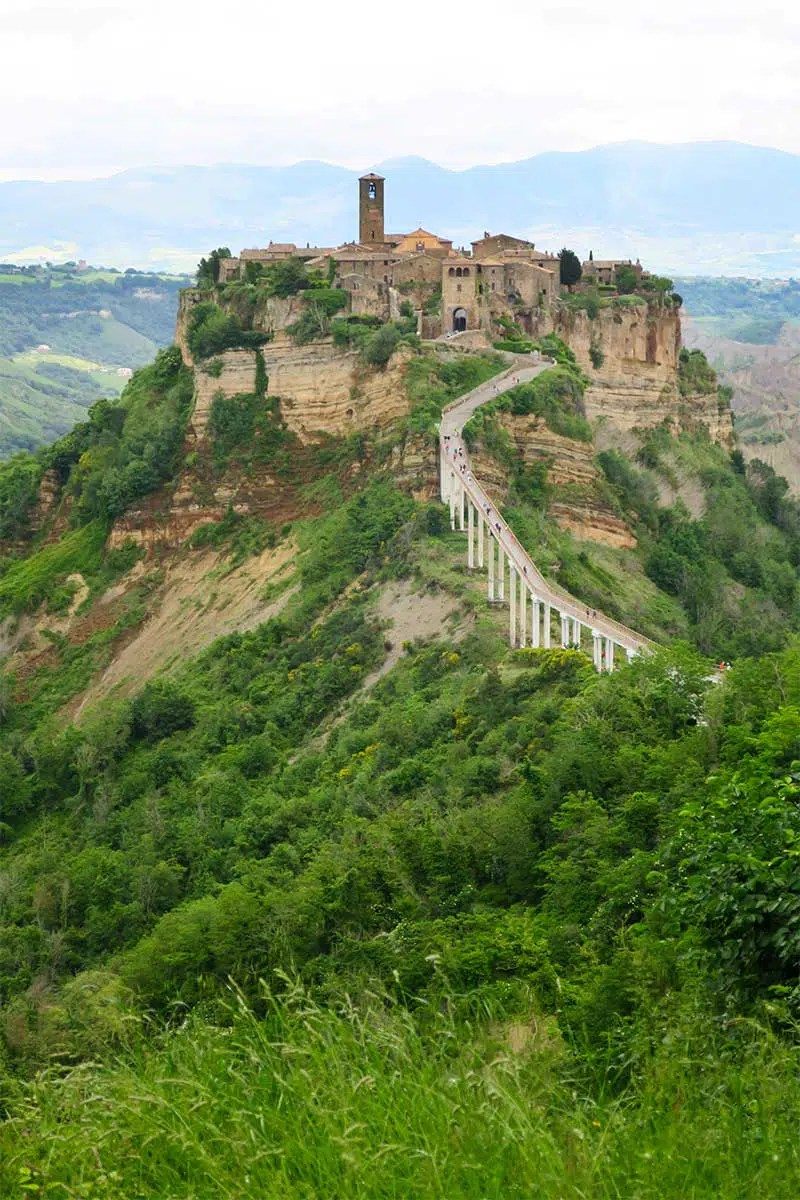 Hazy picture of a green valley surrounded by hills and a long road leading up to a hill top village in Italy. Civita di Bagnoregio was one of the amazing places I visited in 2018. Read my travel year review to find out more