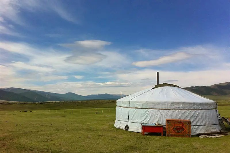 White round Mongolian nomad tent with bright red cushions in front of it. The tent sits in a green grass meadow against a bright blue sky with white fluffy clouds.