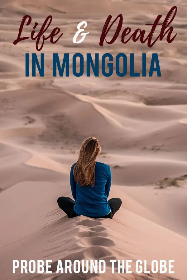 Young woman with long flowing hair sits in the sand on a pink sand dune in Mongolia, looking into the distance. Text overlay saying: Life and Death in Mongolia. Probe around the Globe