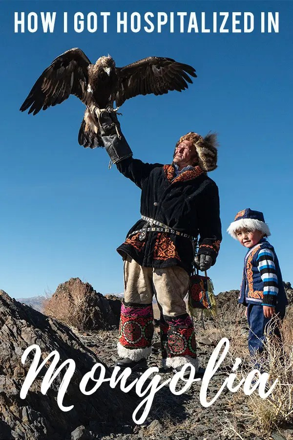 Mongolian hunter in traditional clothes holding out his arm where an falcon just lands with a small boy standing besides him with a round hat with white bunny skinned rim. text overlay staying: how I got hospitalized in Mongolia.