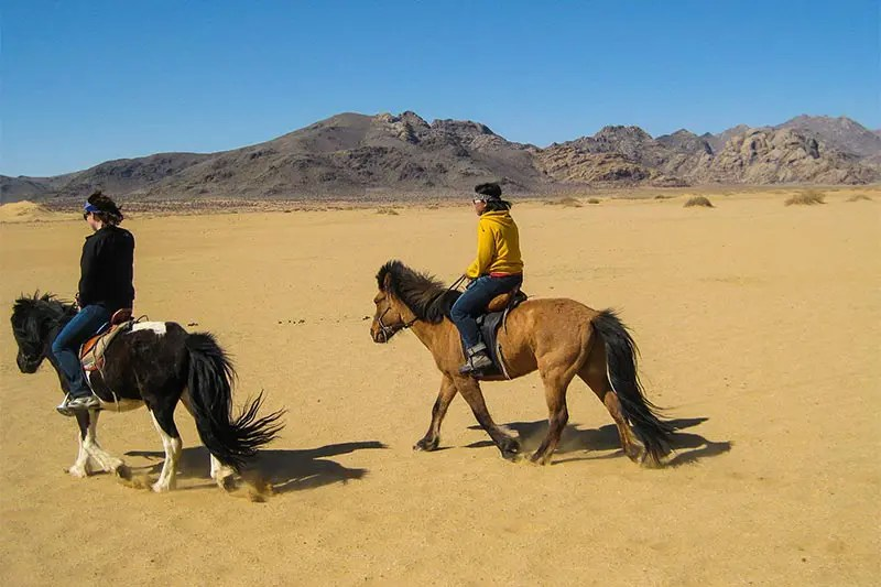 Young female solo traveler with local Mongolian guide riding Mongolian horses in the Mongolian desert.