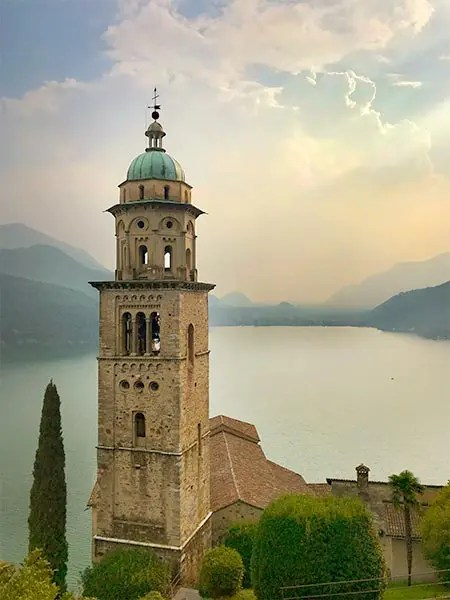 Bell tower of Morcote village overlooking Lake Lugano right before a storm rolls in over this beautiful city in Switzerland. #switzerland #beautifulplaces #lugano #swisstowns #swissalps