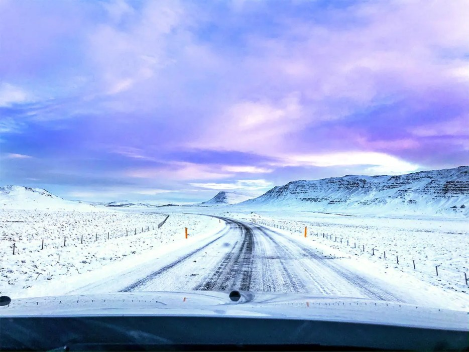 Snow-covered road cutting through snowy mountains under a bright purple and pink cloud covered sky during sunrise in Iceland.