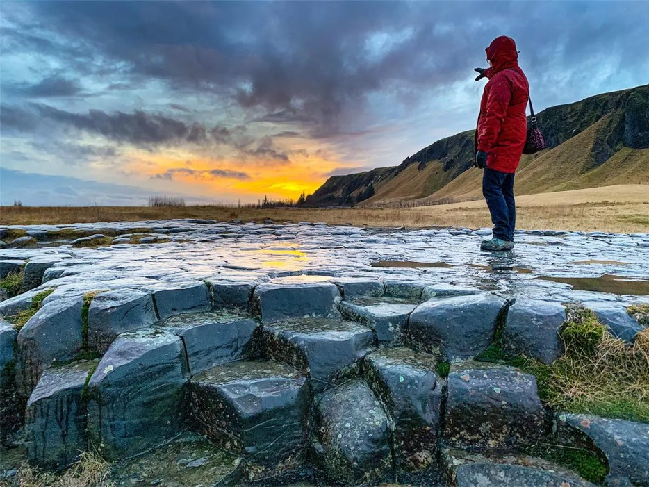 Woman standing on basalt hexagon-shaped rocks, pointing to the mountains and sunset in the distance