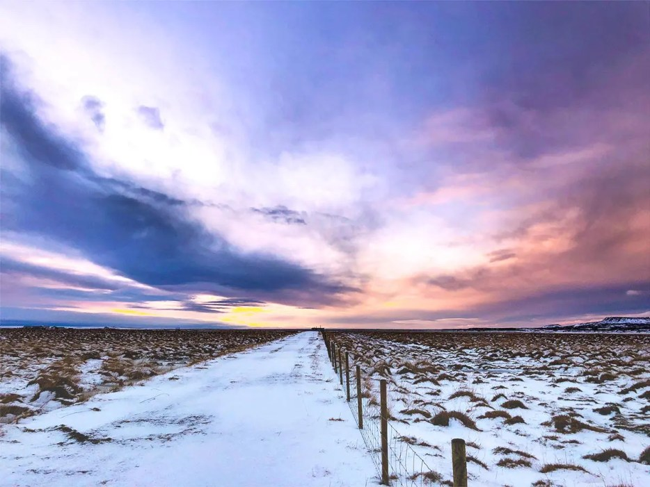 Snow covered road cutting a field in half with a soft colored sunrise above it. Dark clouds turning the sky purple and soft orange.