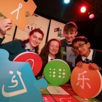 Four students pictured holding large puzzle pieces