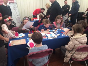 Children sitting at table cutting out circular shapes on card