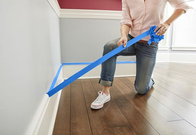 woman removing painters tape. avoid painting mistakes by using painters tape