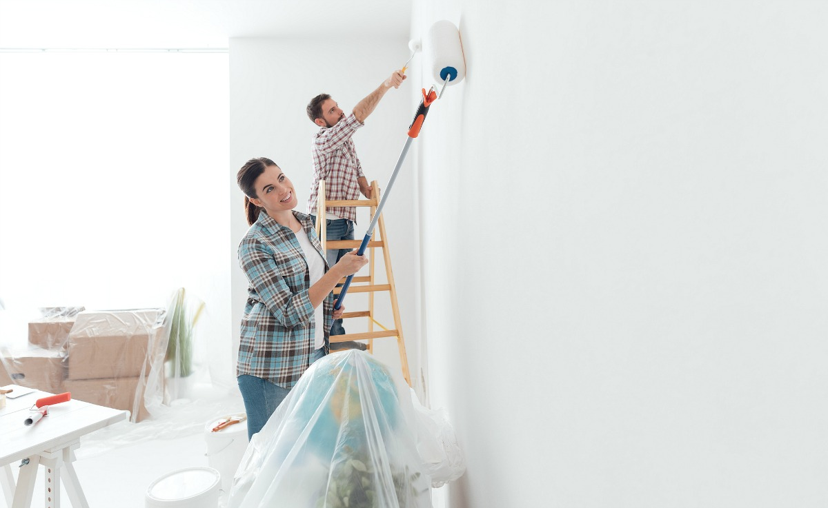 a happy couple paints a wall in their house
