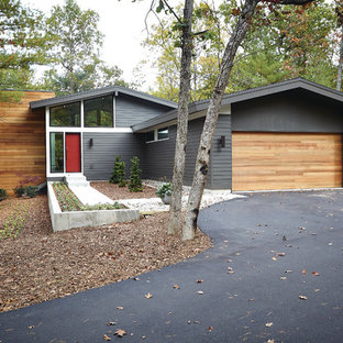 Grey mid century modern house with wooden accents and red door
