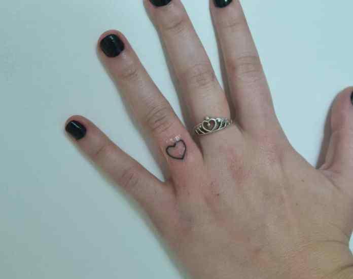 Un pequeño corazón como tatuaje en dedo