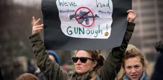 mujer sostiene pancarta en contra del uso de armas