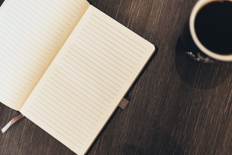 Notebook on a wooden table with a coffee
