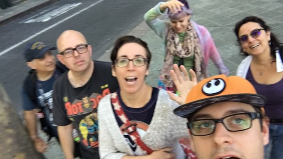 A group of happy sleepy people slightly blurry as a selfie. We are outside.