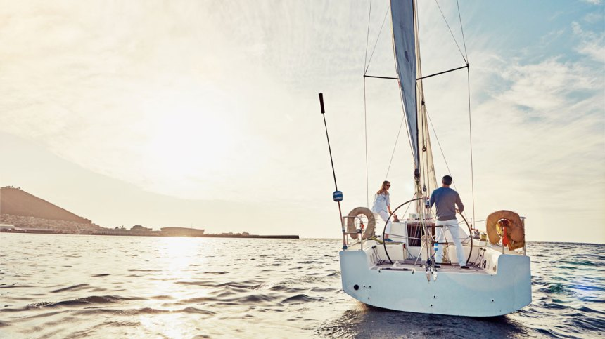 A man and woman stand aboard a sailboat on the open water.