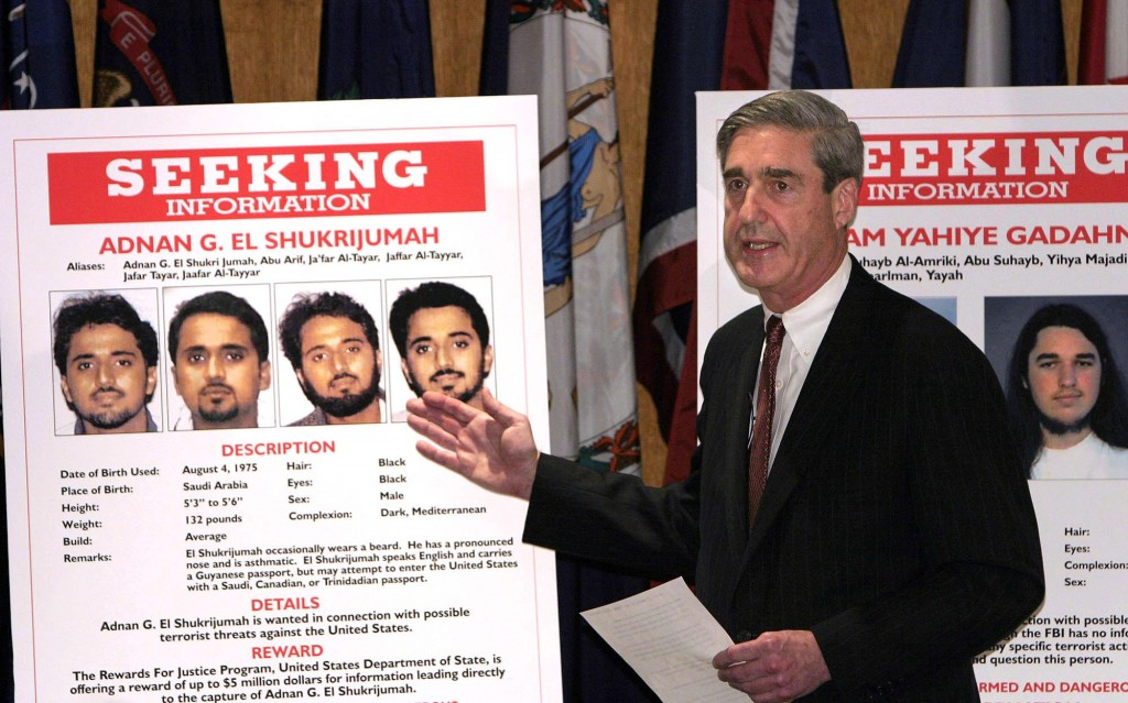 "UNITED STATES - MAY 26:  FBI Director Robert S. Mueller III gestures toward a placard bearing photos of suspected terrorist Adnan G. El Shukrijumah at a news conference in Washington, DC on Wednesday, May 26, 2004. The U.S. has ""credible intelligence from multiple sources"" that al-Qaeda plans to attack the U.S. in the next few months, Attorney General John Ashcroft said.  (Photo by Dennis Brack/Bloomberg via Getty Images)"