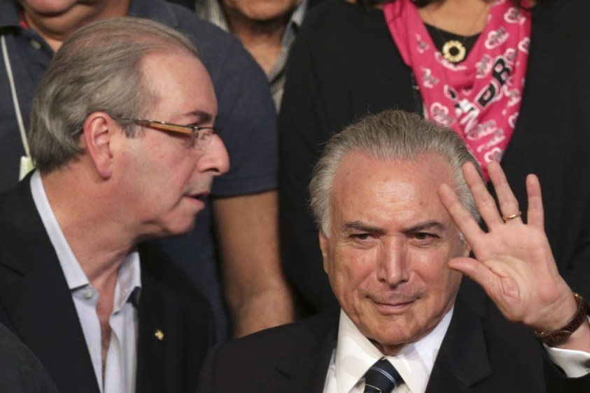 Brazil's Vice President Michel Temer waves during the Brazilian Democratic Movement Party, (PMDB), national convention in Brasilia, Brazil, Saturday, March 12, 2016. The PMDB is considering abandoning its alliance with the Workers' Party that began during Luiz Inacio Lula da Silva's government. Silva served as Brazil's president from Jan. 2003 to Jan. 1 2011. Pictured on left is the speaker of Brazil's lower house of Congress Eduardo Cunha. (AP Photo/Eraldo Peres)